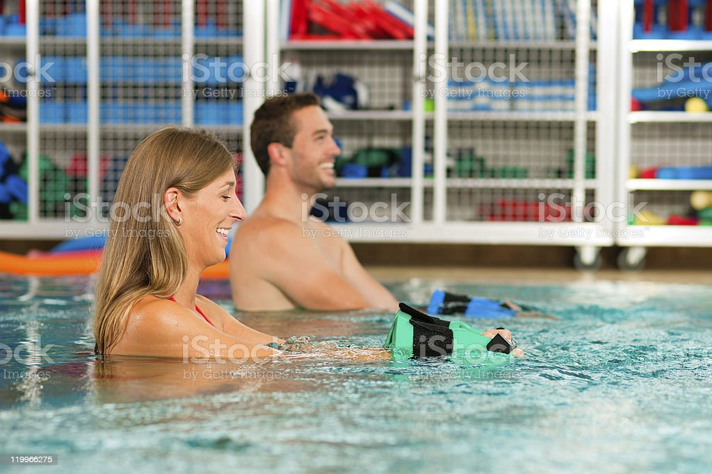 Couple in a pool doing Aquarobics stock photo
