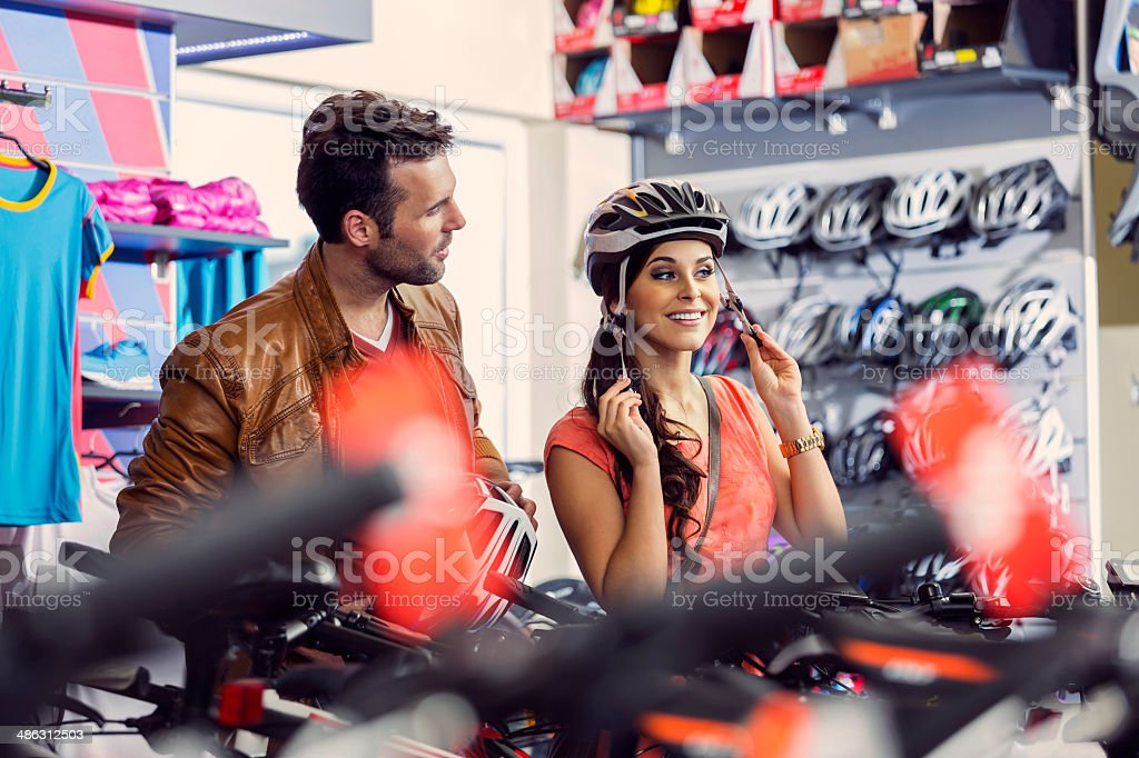 Couple in a sports shop Young woman trying on a cycling helmet in bike shop, her partner giving her some advices. 20-24 Years Stock Photo