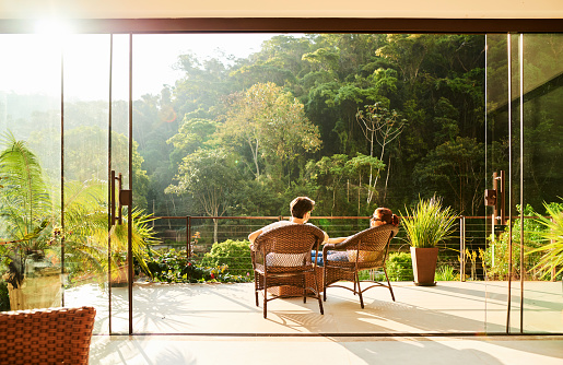 Rear view of a couple relaxing in the chairs at hotel balcony