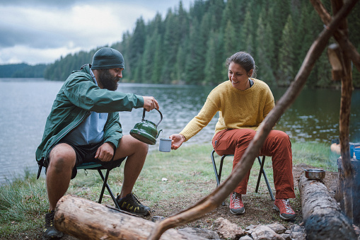 Adventures couple is sitting next to the campfire at  the camping area drinking tea and smiling