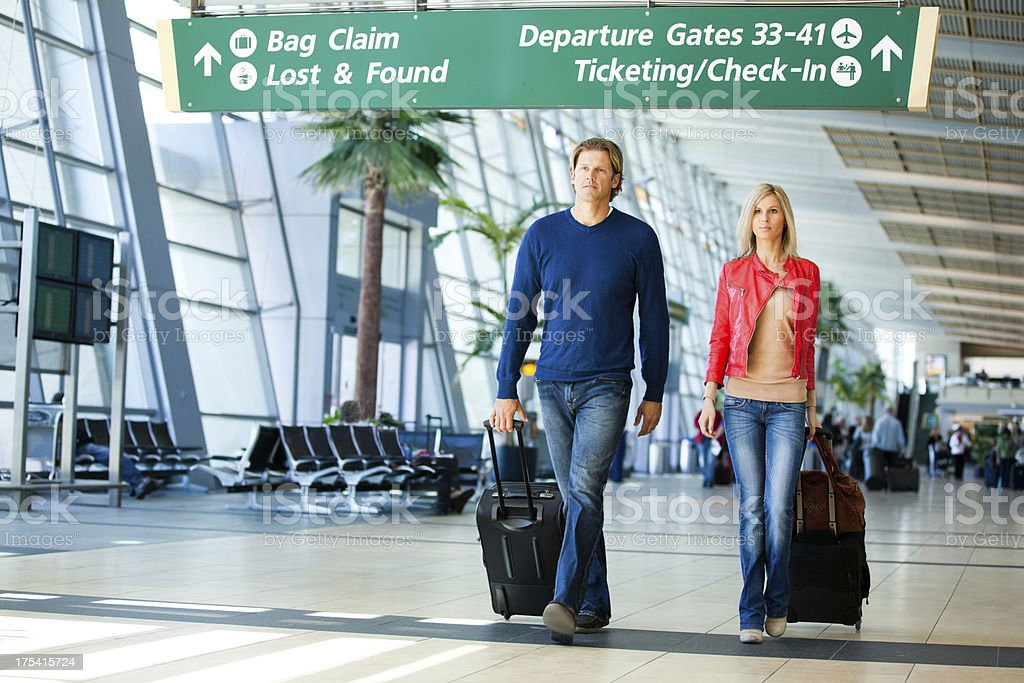 Couple in an airport with suitcases. royalty-free stock photo