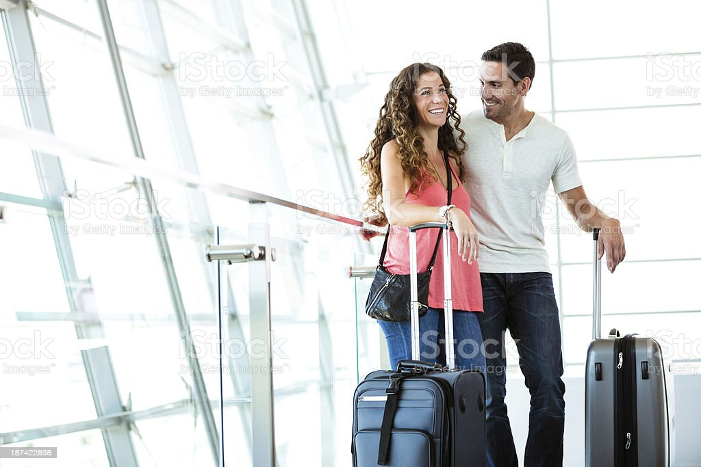 Couple in an airport with suitcases. stock photo