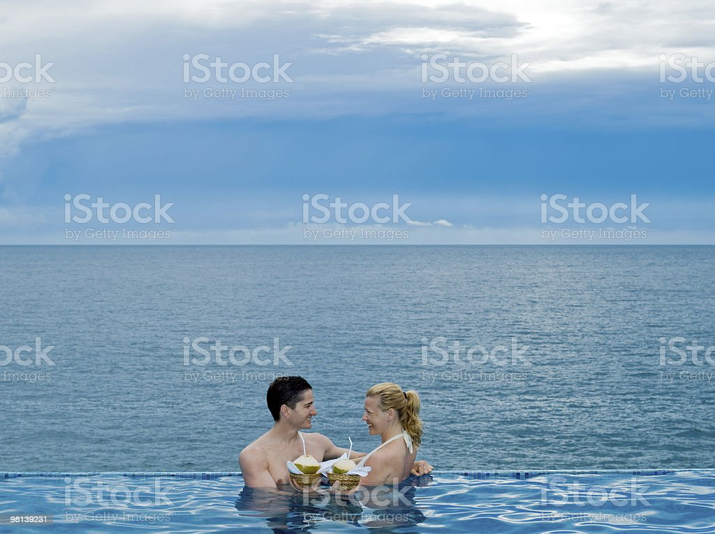 couple in an infinity swimming pool by the sea royalty-free stock photo
