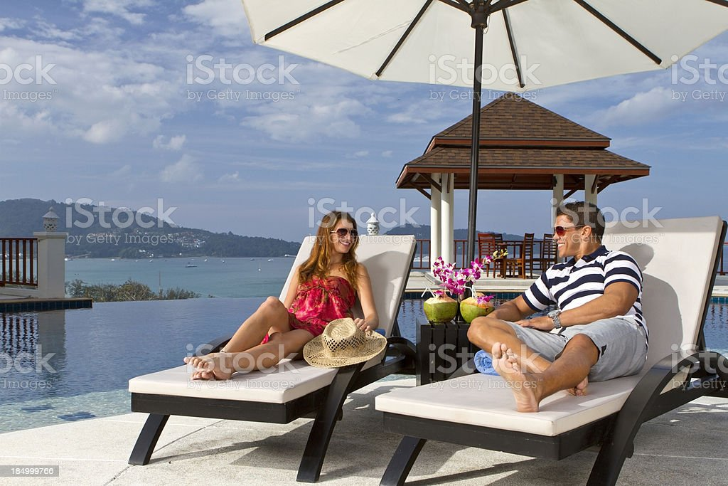 Couple in armchairs near swimming pool stock photo