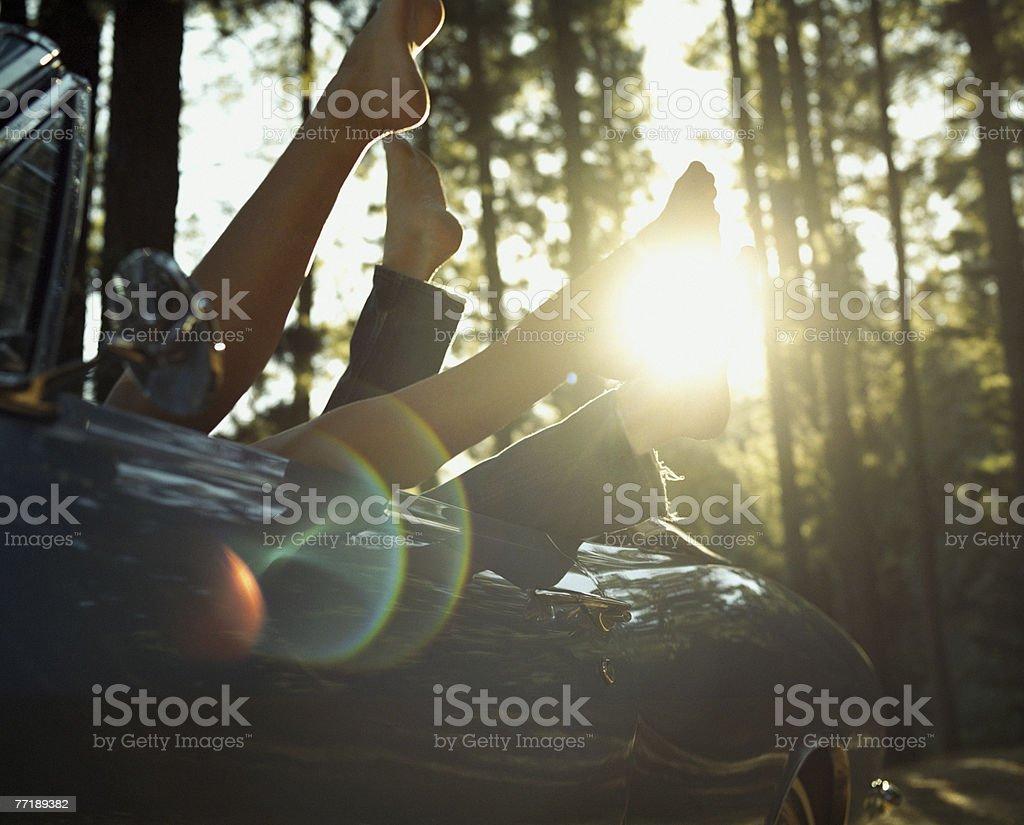 自動車のカップルに、空気中の足 - 20-24歳のロイヤリティフリーストックフォト