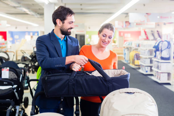 Couple in baby shop buying stroller stock photo