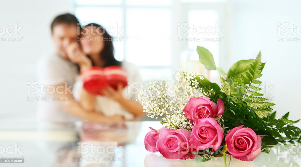 Couple in Background with Roses on Table royalty-free stock photo