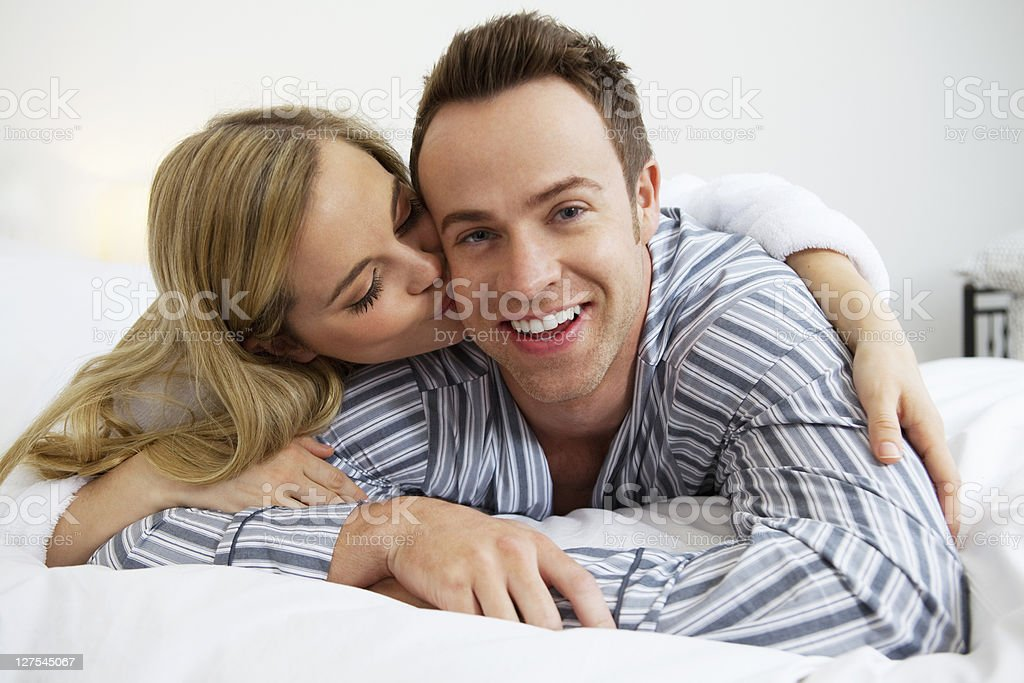 Couple in bathrobes kissing on bed stock photo