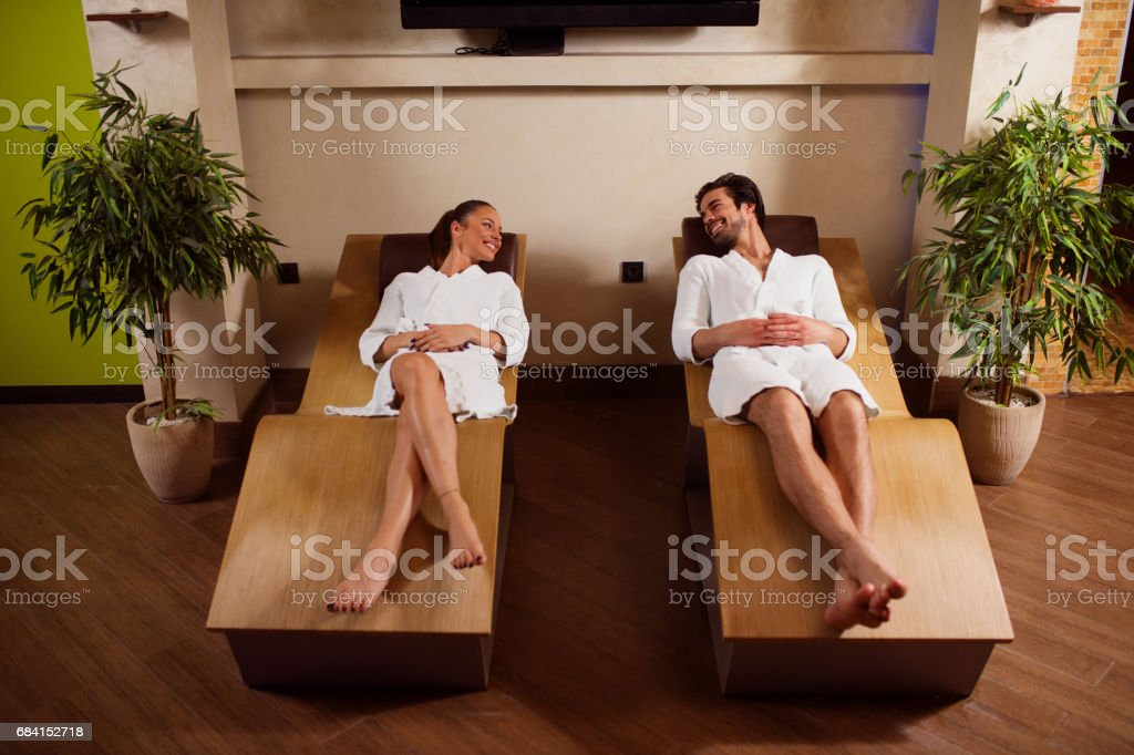 Couple in bathrobes relaxing in lounge chairs at spa zbiór zdjęć royalty-free