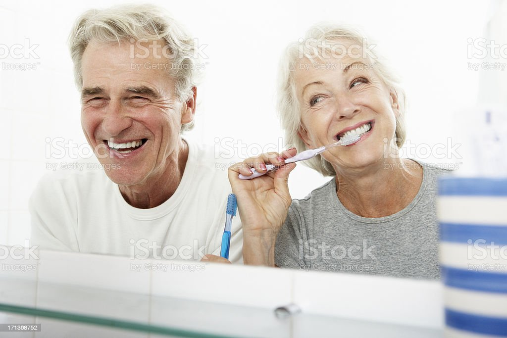 Couple in bathroom with woman brushing her teeth stock photo