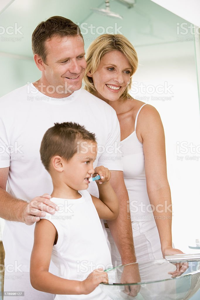 Couple in bathroom with young boy brushing teeth royalty-free stock photo
