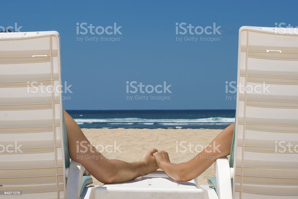 Couple in beach chairs holding hands near ocean stock photo