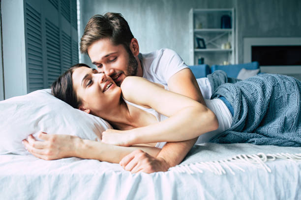 couple in bed at home are kissing each other - łóżko zdjęcia i obrazy z banku zdjęć
