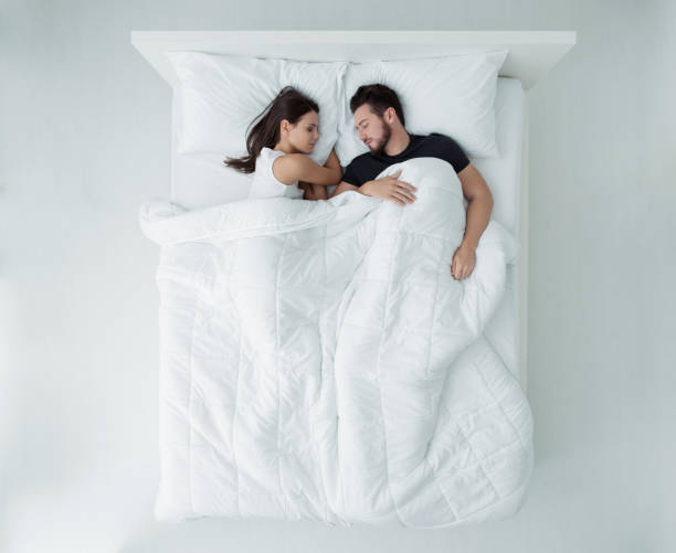 Couple in bed Loving couple relaxing and sleeping in bed, top view couple in bed stock pictures, royalty-free photos & images