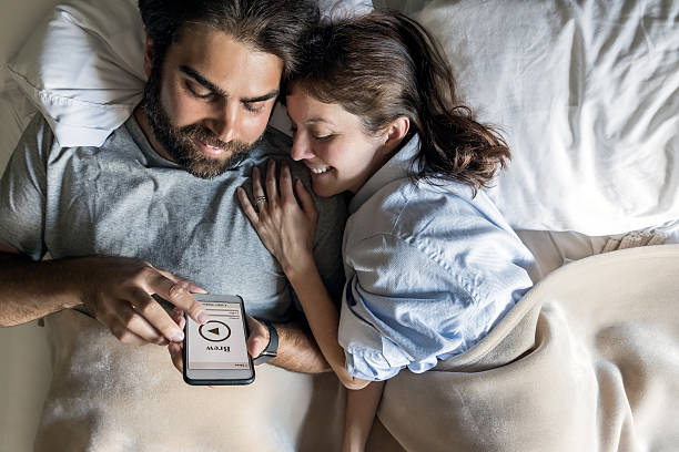 Couple in Bed Using Coffee Maker Application on Smart Phone stock photo
