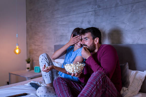 Couple in bed watching scary movie stock photo
