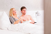 istock Couple in bed watching tv 174968379