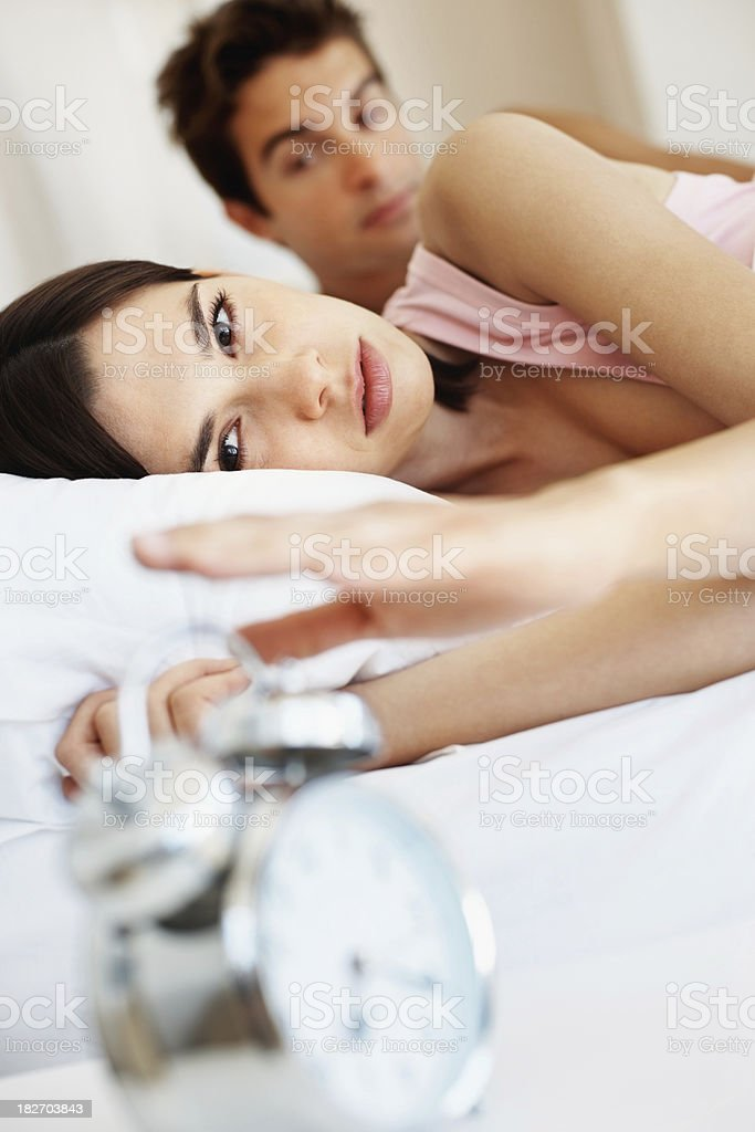 Couple in bed , woman putting off the alarm clock royalty-free stock photo