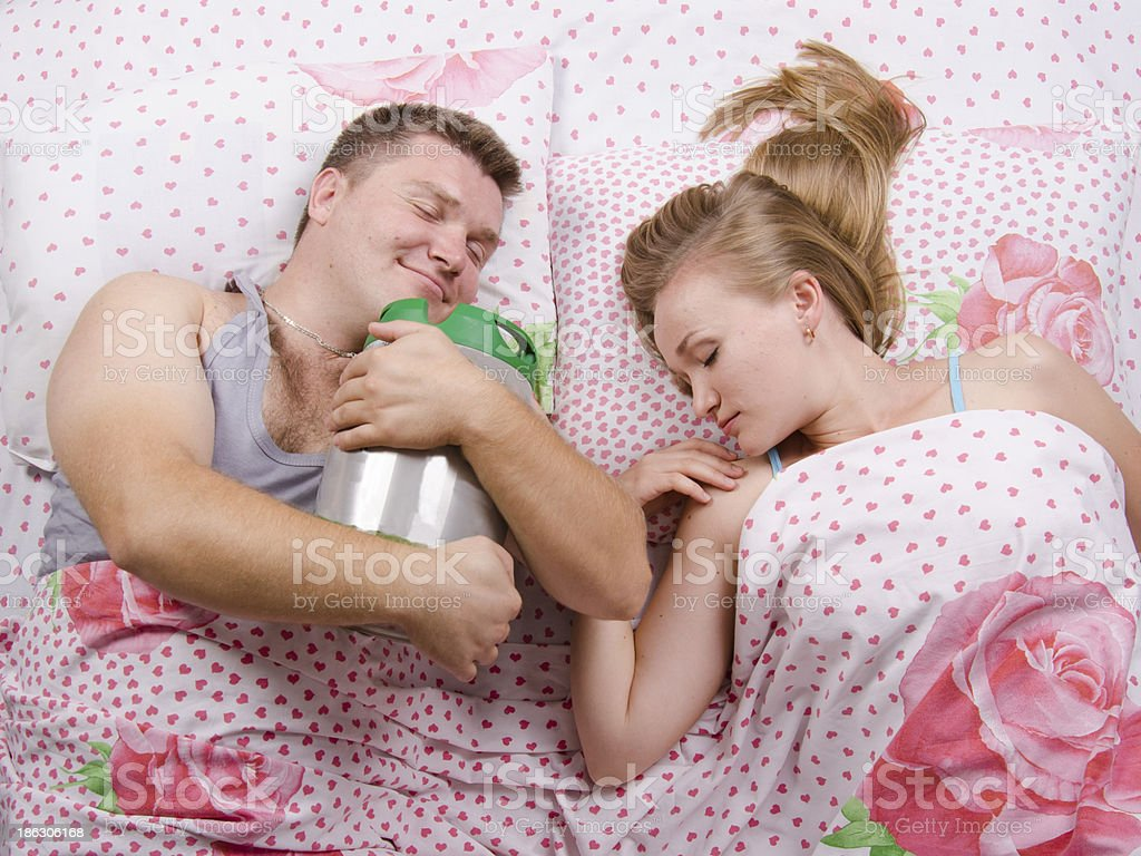 Couple in bed-husband sleeps with barrel of beer royalty-free stock photo