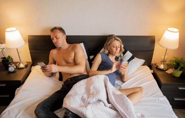Couple in bedroom busy with their mobile phones stock photo