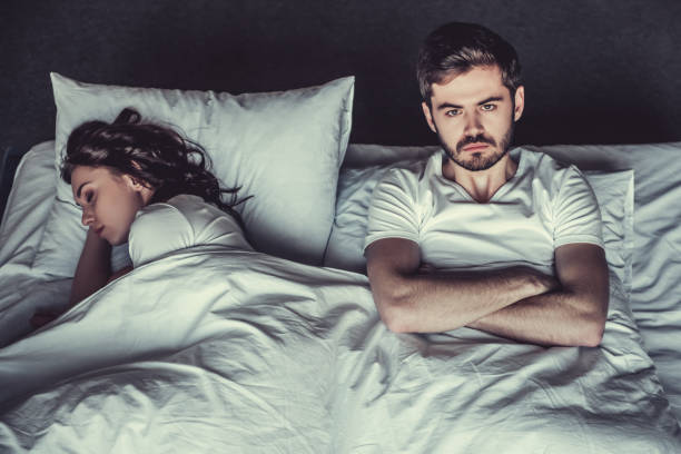 Couple in bedroom Young unhappy man and his girlfriend sleeping in bed. background of the sad couple fighting bed stock pictures, royalty-free photos & images
