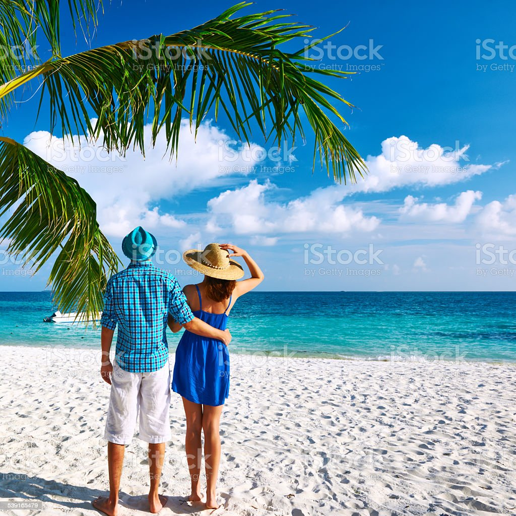 Couple In Blue Clothes On A Beach At Maldives Stock Photo
