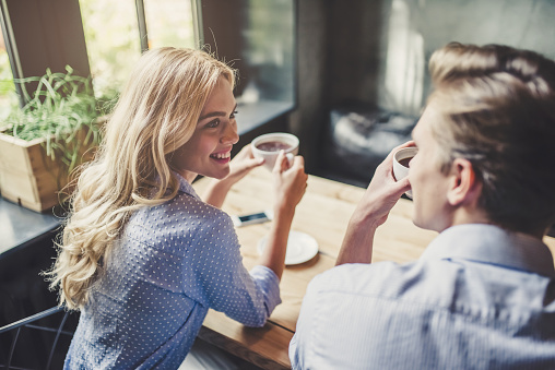 Handsome young man and attractive young woman are spending time together. Romantic couple in cafe is drinking coffee and enjoying being together.