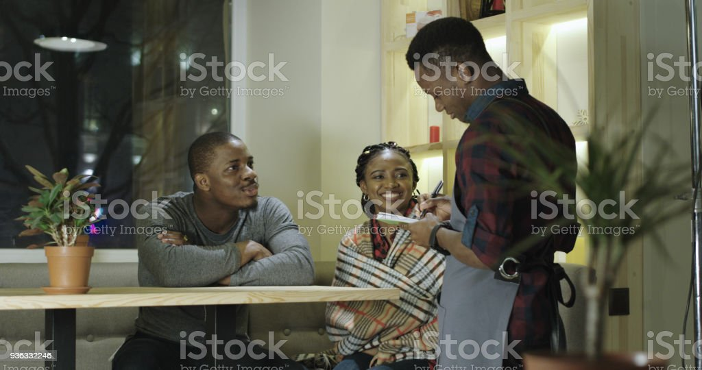 Couple in cafe talking to waiter stock photo