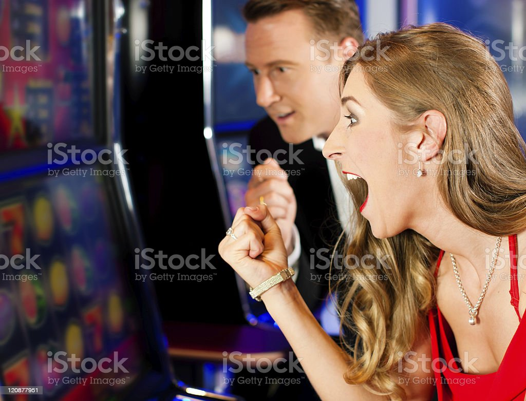 Couple in Casino on slot machine stock photo