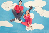 Couple in comic book: Sitting on clouds, thinking