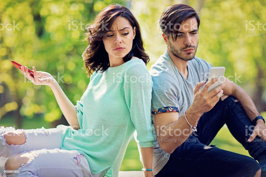 Couple in conflict is texting in the park and sulking each other stock photo