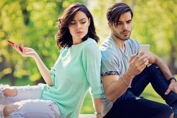 競合しているカップルが公園でお互いをやめなさいテキスト メッセージです。 - 羨望 ストックフォトと画像