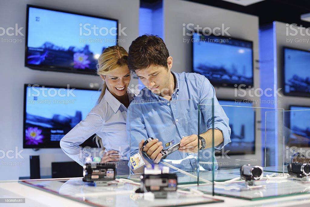 couple in consumer electronics store buying photo camera stock photo