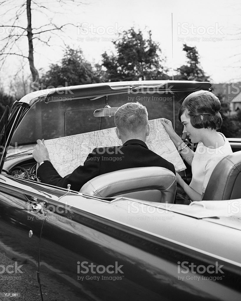 Couple in convertible looking at roadmap royalty-free stock photo