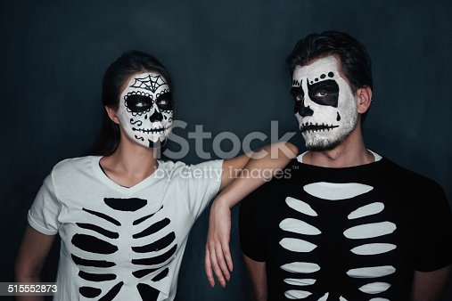 Loving couple with skull face art in costume of skeletons on dark background, Halloween theme