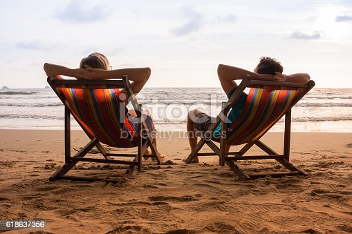 577645320 istock photo Couple in deck chairs at sea beach 618637356