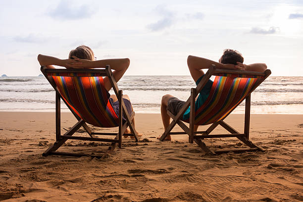 Couple in deck chairs at sea beach stock photo