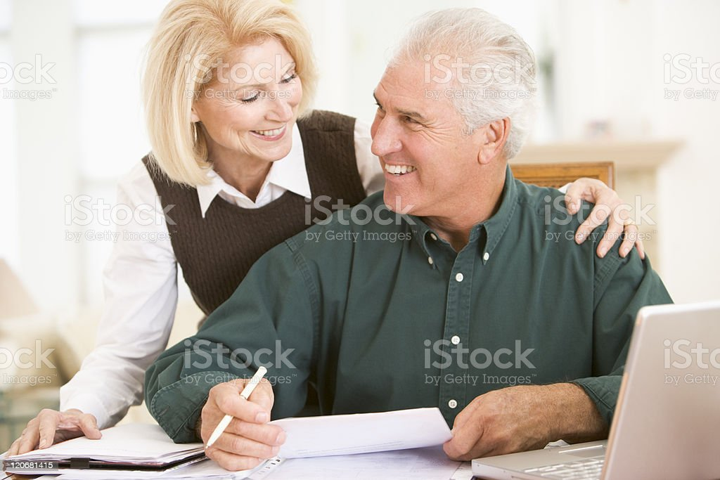 Couple in dining room with laptop doing paperwork smiling royalty-free stock photo