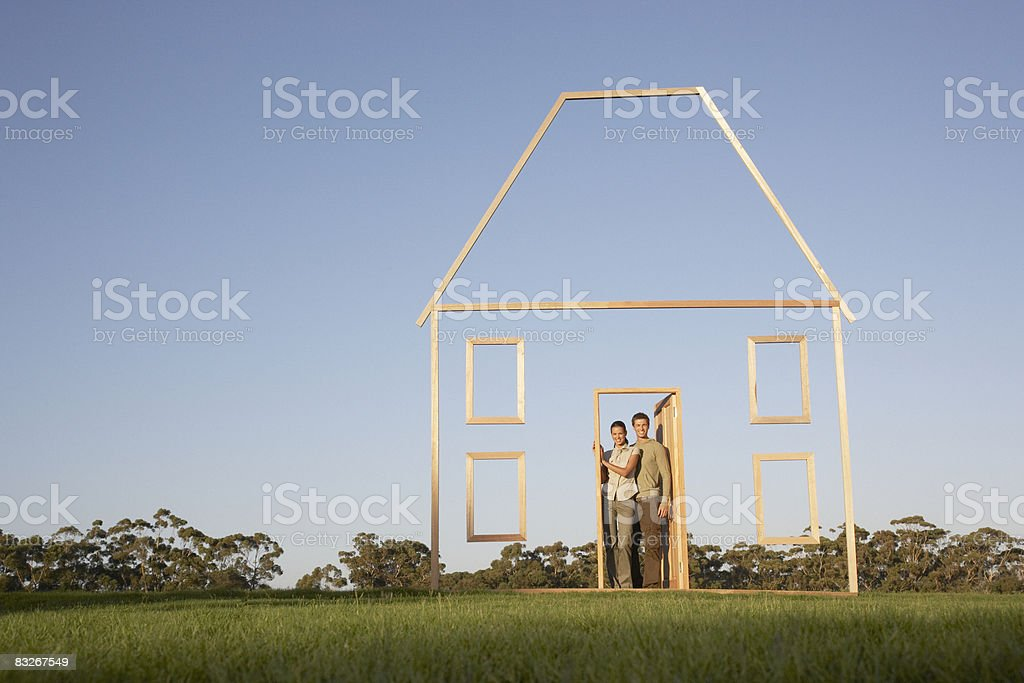Couple in doorway of house outline royaltyfri bildbanksbilder