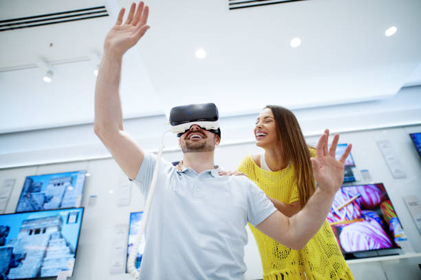 couple in electronics store, exploring vr goggles and having a good time. - happy person buy appliances stock photos and pictures