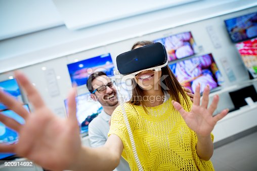 istock Couple in electronics store, exploring VR goggles. 920914692