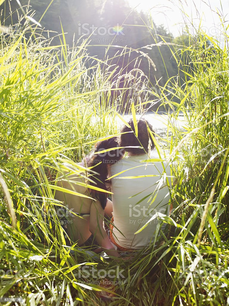Couple in embrace sitting at riverbank photo libre de droits