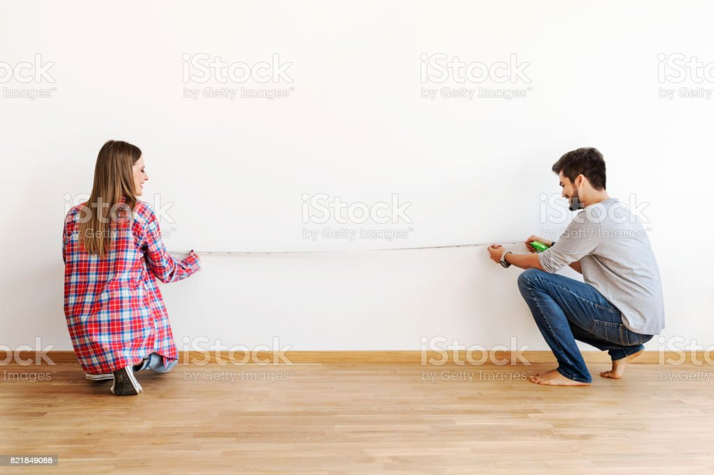 Couple in empty apartment measuring walls stock photo