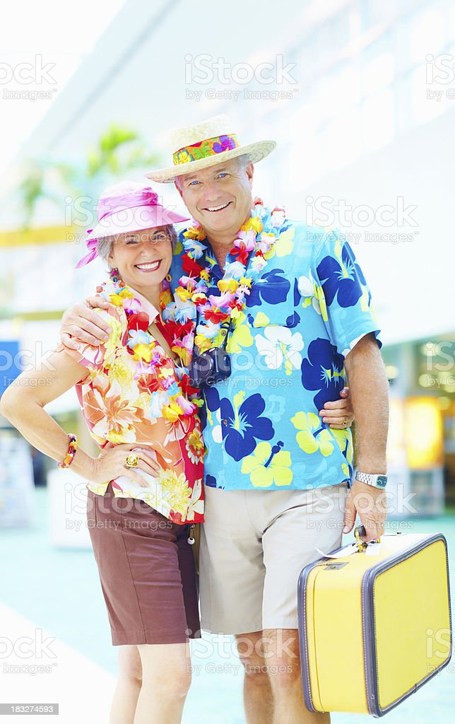 Couple in floral clothing with luggage embracing at an airport royalty-free stock photo