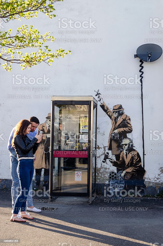 Couple in front of a possible Banksy artwork, Cheltenham stock photo