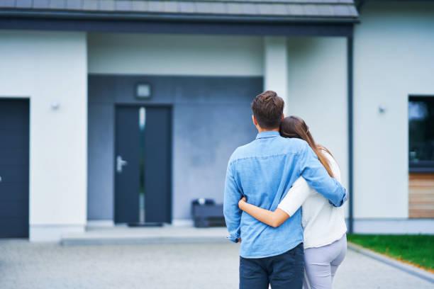 Paar vor Einfamilienhaus in modernem Wohngebiet – Foto