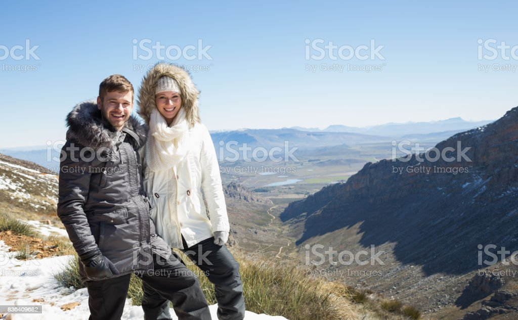 Couple in fur hood jackets against snowed mountainous valley stock photo