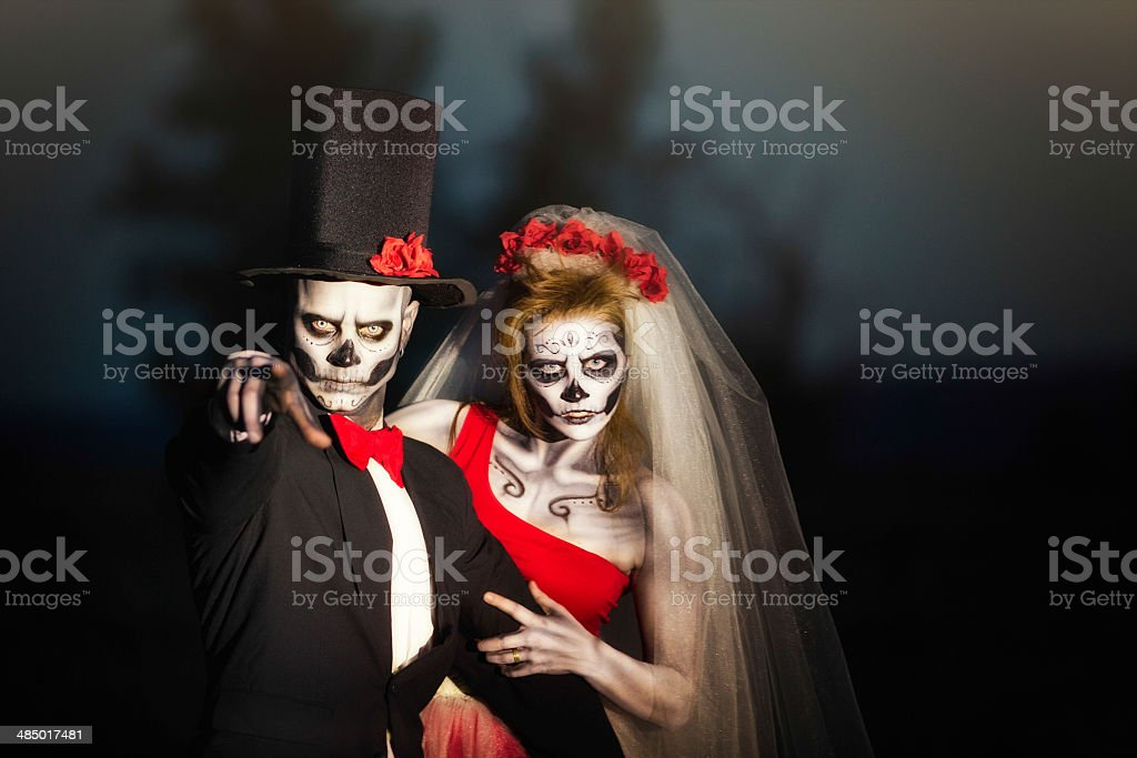 Couple in Halloween skeleton bridal costume does threatening gesture stock photo
