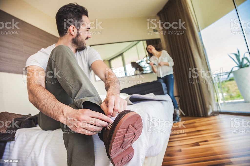 Couple in hotel room getting dressed royalty-free stock photo