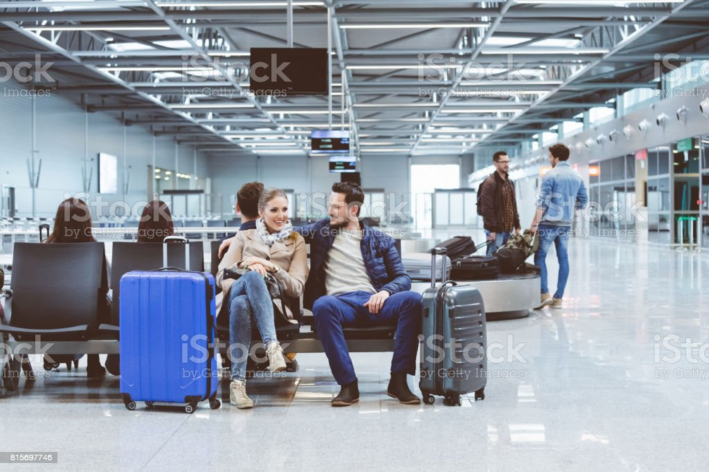 Couple in international airport waiting for flight stock photo